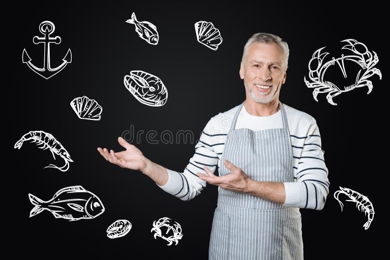 Doświadczony kucbarski ono uśmiecha się podczas gdy oferujący smakowitego morskiego jedzenie fotografia stock