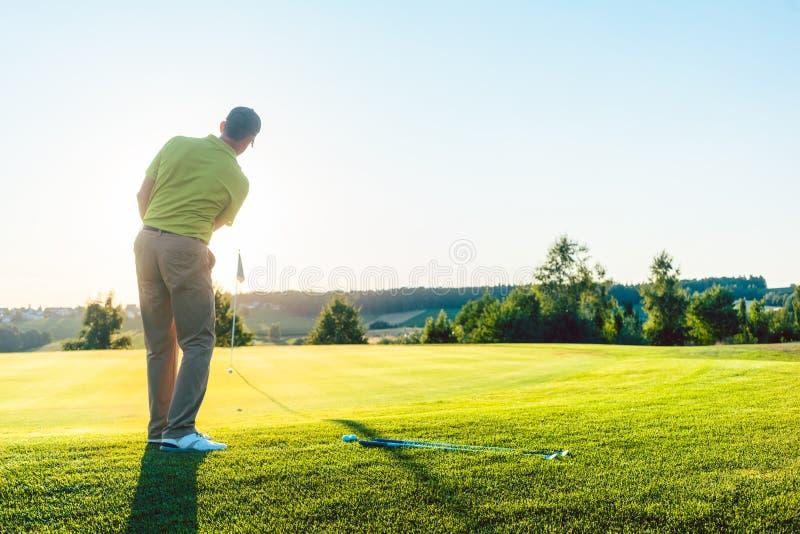 Doświadczony męski golfista uderza piłkę golfową w kierunku filiżanki fotografia stock