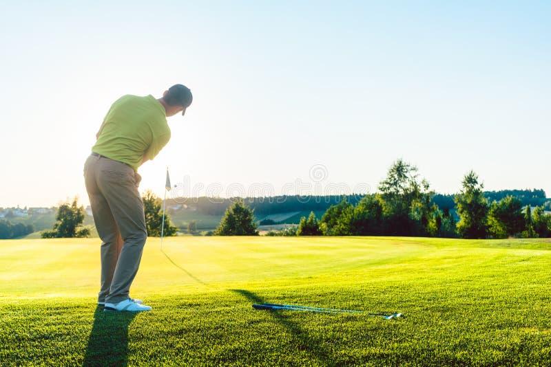 Doświadczony męski golfista uderza piłkę golfową w kierunku filiżanki obraz stock