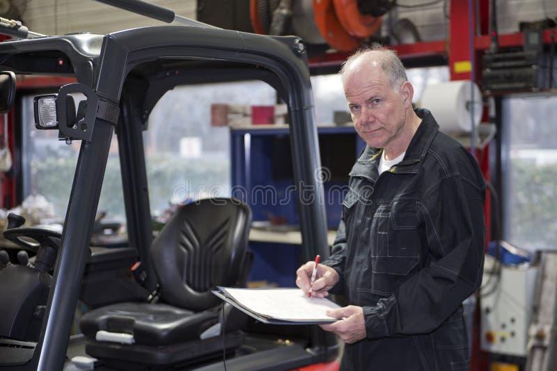 Doświadczony mechanik iść nad listą kontrolną zdjęcia royalty free