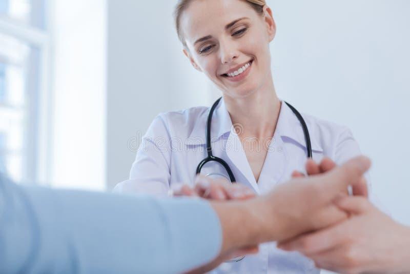 Doświadczony student medycyny sprawdza cierpliwego tętno w medycznym gabinecie obraz stock