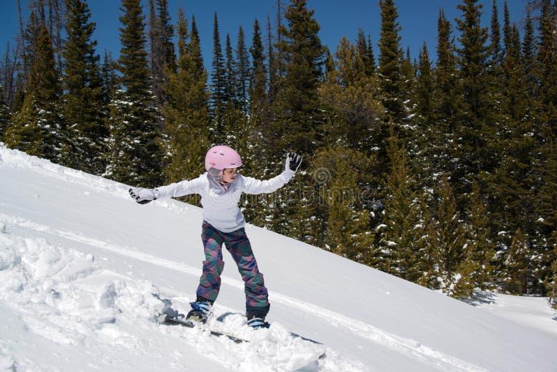 Do adolescente da snowboarding monte nevado para baixo nas montanhas imagem de stock