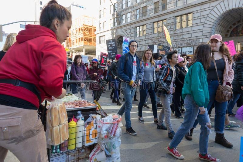 2do ` anual s marzo de las mujeres - vendedor y manifestantes del perrito caliente fotografía de archivo