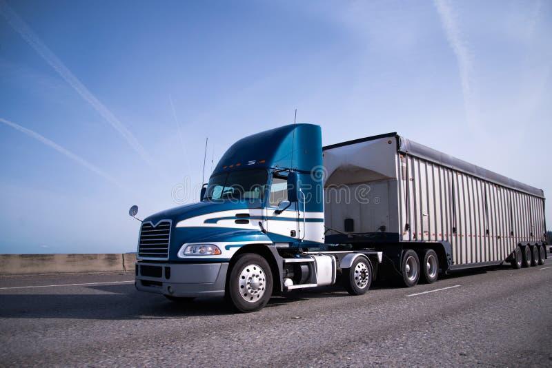 Do azul caminhão moderno semi com táxi do dia e reboque do volume no intersta imagem de stock royalty free