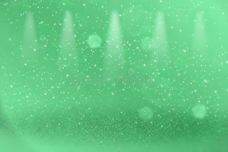 Do bokeh defocused dos projetores da fase das luzes do brilho o fundo abstrato de brilho bonito verde com faíscas voa, textura fe ilustração royalty free