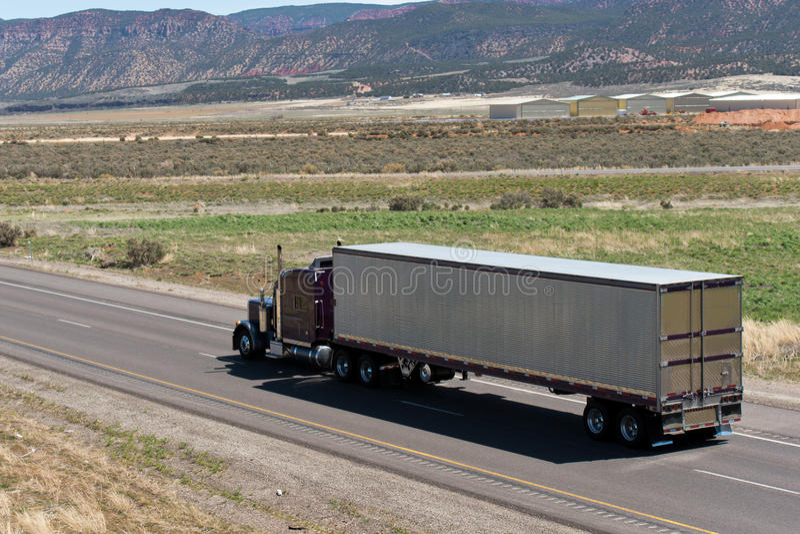 Do clássico caminhão e reboque escuros semi na estrada com opinião da natureza foto de stock