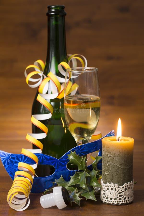 Do dia anos novos da vida ainda com garrafa do champanhe, vidro, e vela de queimadura foto de stock royalty free