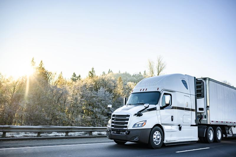 Do equipamento caminhão grande à moda branco semi que transporta a carga perecível no caminhão do refrigerador semi que corre na  imagem de stock royalty free