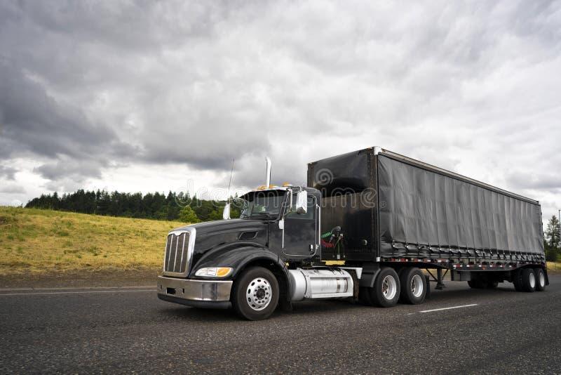 Do equipamento caminhão grande à moda preto semi para o transporte local que transporta o carro fotografia de stock royalty free