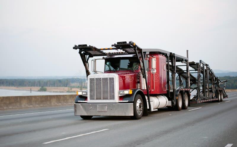 Do equipamento caminhão grande clássico vermelho semi com o reboque do alador do carro que corre b fotos de stock