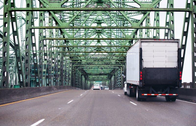 Do equipamento caminhão grande semi com levantamento da estrada indo alo da unidade da porta traseira fotos de stock