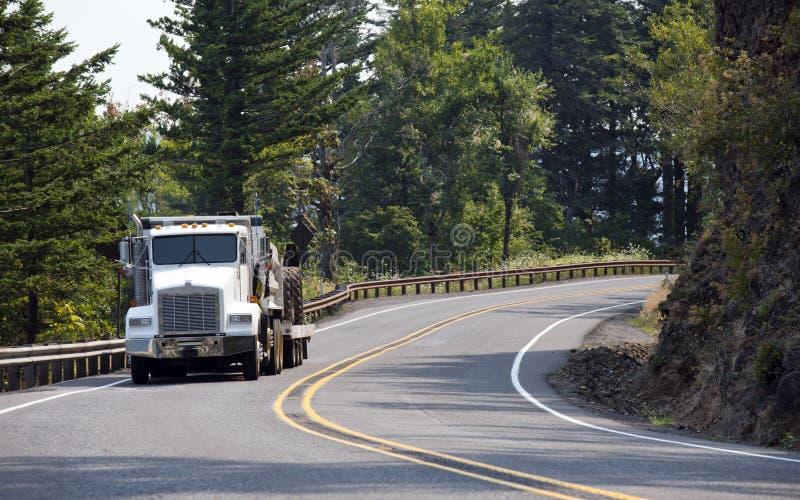 Do equipamento do clássico caminhão grande semi que transporta o equipamento de construção a foto de stock