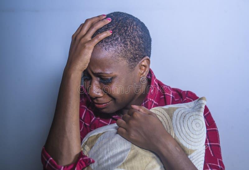 Do estilo de vida retrato dentro da mulher afro-americana preta triste e deprimida nova que senta em casa o sentimento do assoalh fotografia de stock royalty free