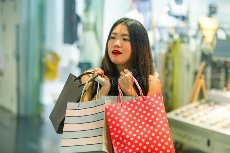 Do estilo de vida retrato dentro de sacos de compras levando novos da mulher coreana asiática feliz e bonita na alameda que compr imagens de stock