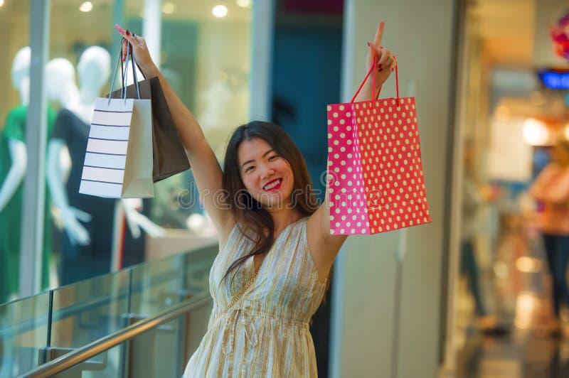 Do estilo de vida retrato dentro de sacos de compras levando novos da mulher coreana asiática feliz e bonita na alameda que compr imagem de stock