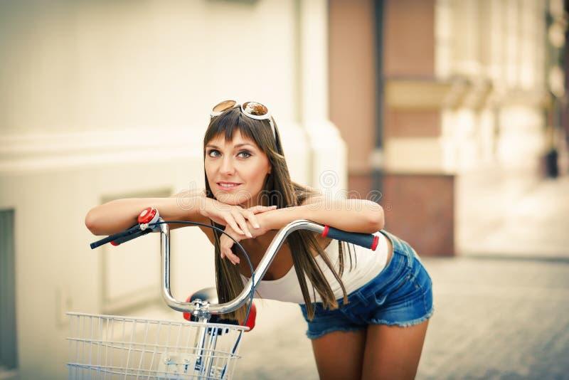 Do estilo retro consideravelmente 'sexy' do moderno da mulher dos jovens o retrato exterior com com a bicicleta vermelha tem o di imagem de stock