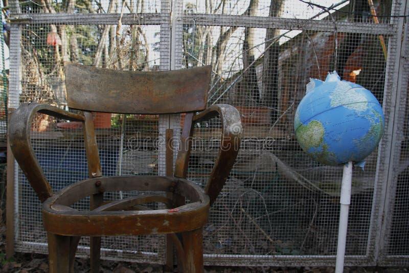Do góry nogami kula ziemska i drewniany krzesło w zaniechanym miejscu Światowy do góry nogami pojęcie obraz royalty free