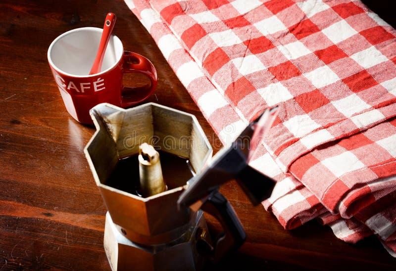 Do guardanapo quadriculado na tabela de madeira com o copo de café vermelho imagem de stock royalty free