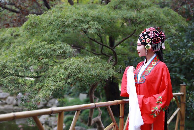 Do jardim chinês do pavilhão dos trajes de Opera de Pequim de Peking da mulher de Aisa a dança tradicional do vestido do jogo do  foto de stock