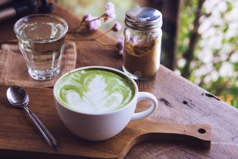 Do latte quente da bebida do ch? verde o copo branco no aroma de madeira da tabela relaxa o tempo na cafetaria foto de stock royalty free