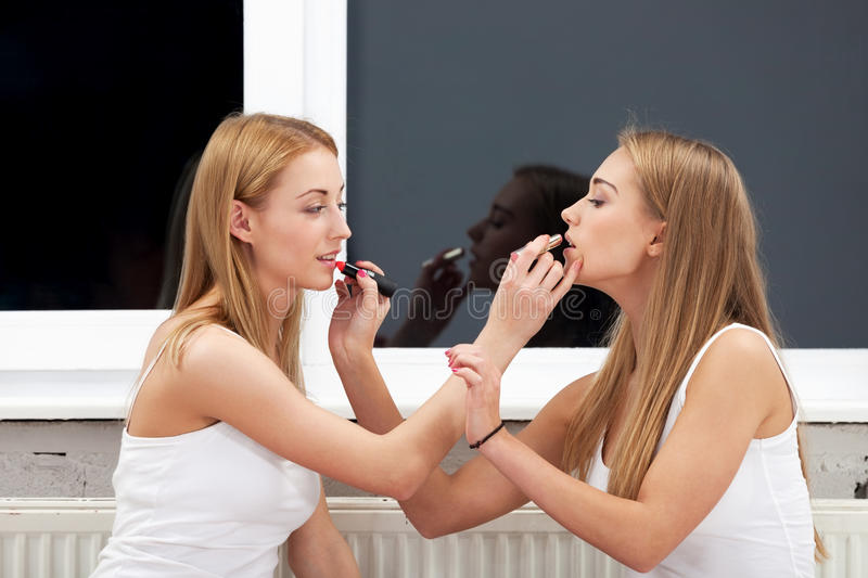 Do me a favor. Two girls applying make up to each other stock photos