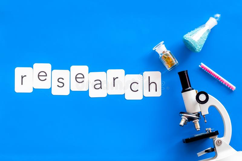 Do medical research with microscope, research copy, test-tubes in lab on blue background top view. Desk of doctor. Do medical research with microscope, research stock photography
