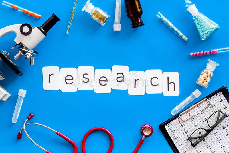 Do medical research with microscope, stethoscope, test-tubes, research copy in lab on blue background top view. Desk of doctor. Do medical research with royalty free stock photography