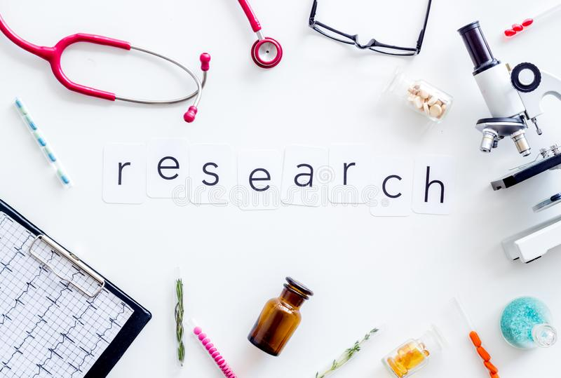 Do medical research with microscope, stethoscope, test-tubes, research copy in lab on white background top view. Desk of doctor. Do medical research with stock images