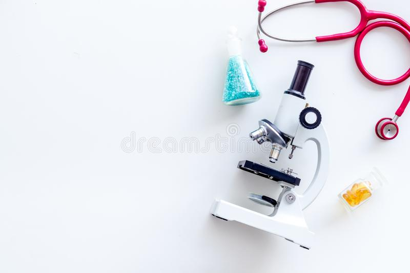 Do medical research with microscope, stethoscope, test-tubes in lab on white background top view mock-up. Desk of doctor. Do medical research with microscope stock photos