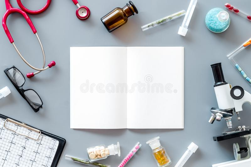 Do medical research with microscope, stethoscope, test-tubes, notebook in lab on gray background top view mockup. Desk of doctor. Do medical research with stock photo