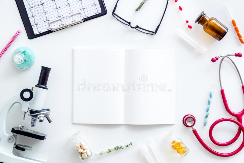 Do medical research with microscope, stethoscope, test-tubes, notebook in lab on white background top view mockup. Desk of doctor. Do medical research with royalty free stock photography