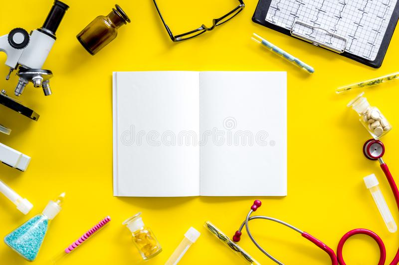 Do medical research with microscope, stethoscope, test-tubes, notebook in lab on yellow background top view mockup. Desk of doctor. Do medical research with royalty free stock images