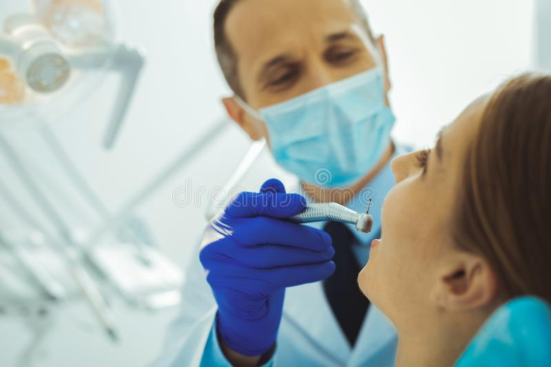 Close up of female person that keeping mouth opened. Do not be scared. Delighted medical worker using special equipment while filling a tooth stock image