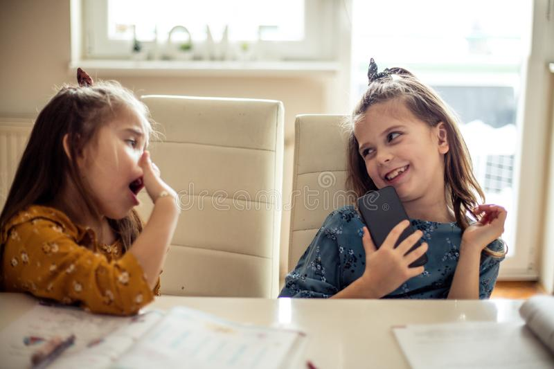 Do not call mom. Two little school little girls at home. Copy space royalty free stock photography