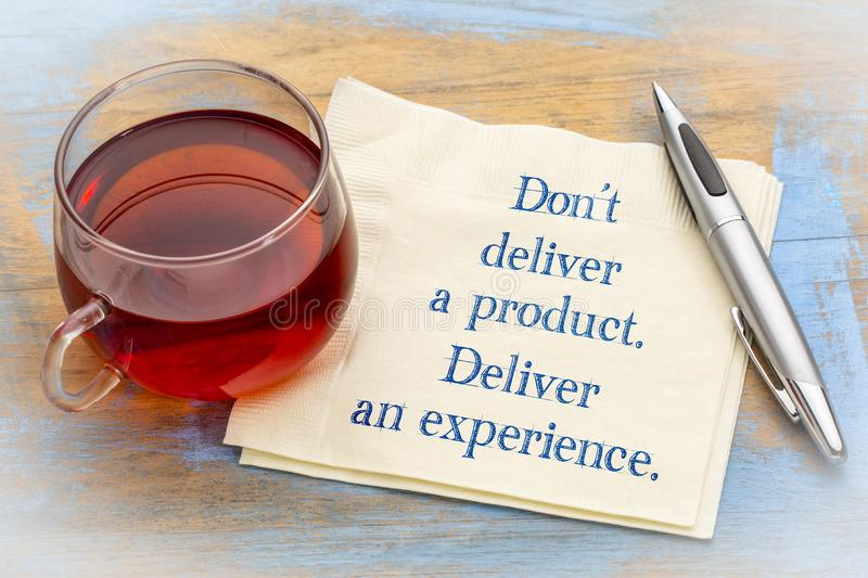 Do not deliver a product, but experience. Don`t deliver a product. Deliver an experience. Handwriting on a napkin with a cup of tea stock photo