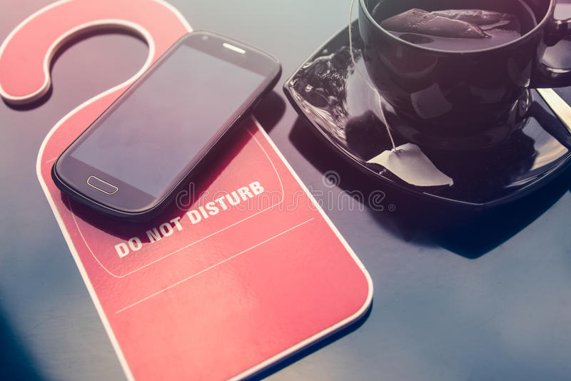Do not disturbe sign, a cup of tea and a mobile phone over dark background. Time for rest concept. royalty free stock photography