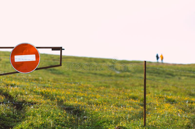 Do not enter sign Green Valley A couple of people in defocus in nature. Do not enter sign Green Valley A couple of people in defocus stock photography