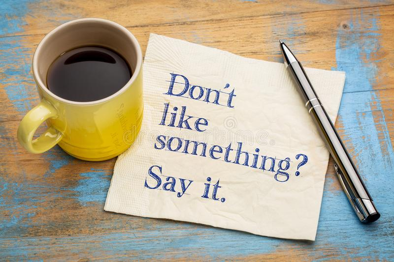 Do not like something? Say it. Handwriting on a napkin with a cup of espresso coffee royalty free stock photo