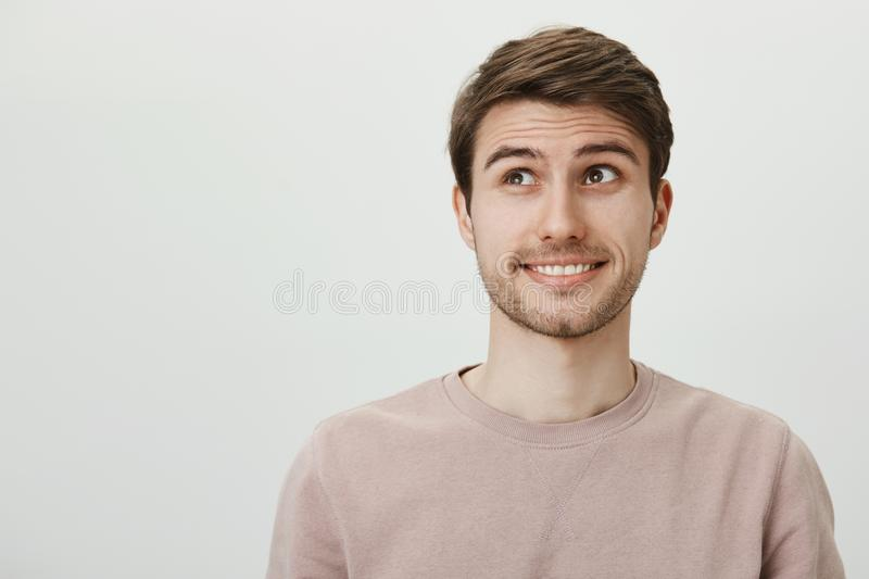 Do not look at me it was not my fault. Careless good-looking caucasian guy with bristle lifting eyebrows and looking. Aside, smiling awkwardly, wanting to hide stock photo