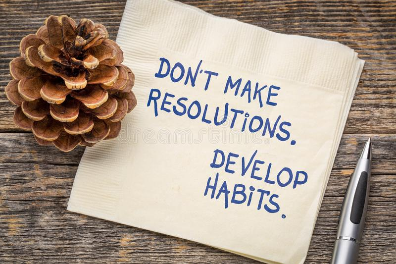 Do not make resolutions, develop habits. Inspirational handwriting on a napkin with a pine cone royalty free stock image