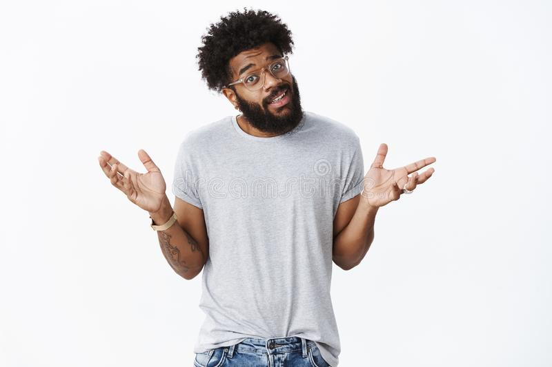 Do not make scene it silly. Careless chill and indifferent african bearded guy in glasses shrugging with raised hands in. Not big deal gesture shrugging being royalty free stock image