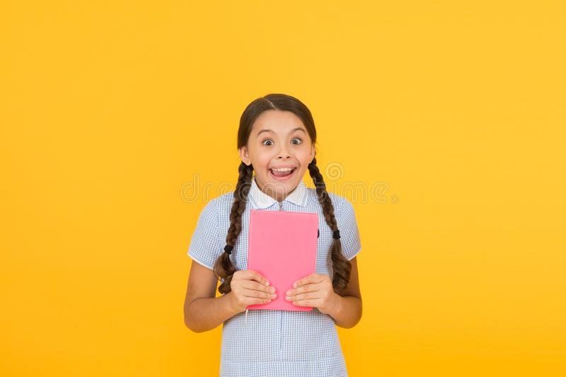 Do not panic. Hysterical laugh. Cute small child reading book on yellow background. Adorable little girl learn reading royalty free stock image