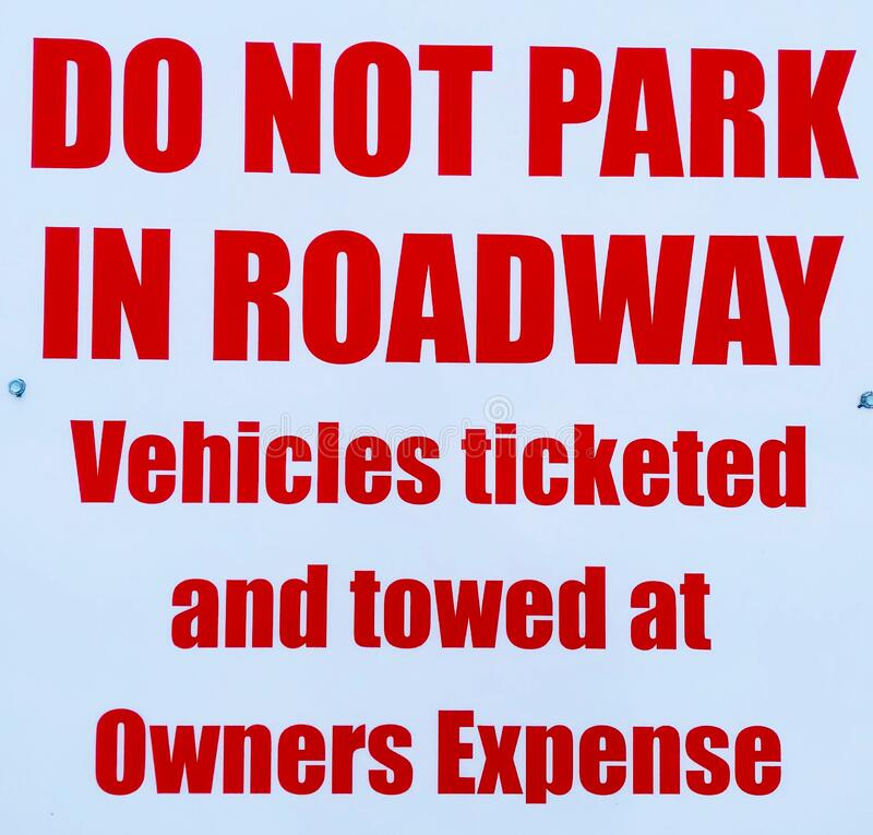 Do not park in roadway. Do not park in roadway vehicles ticketed and towed at owners expense royalty free stock photography