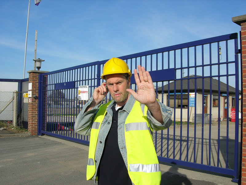 Do not pass. A work site gate supervisor wearing hige visability vest and yellow hard hat raises his hand to stop visitors while using his mobile phone to get stock image