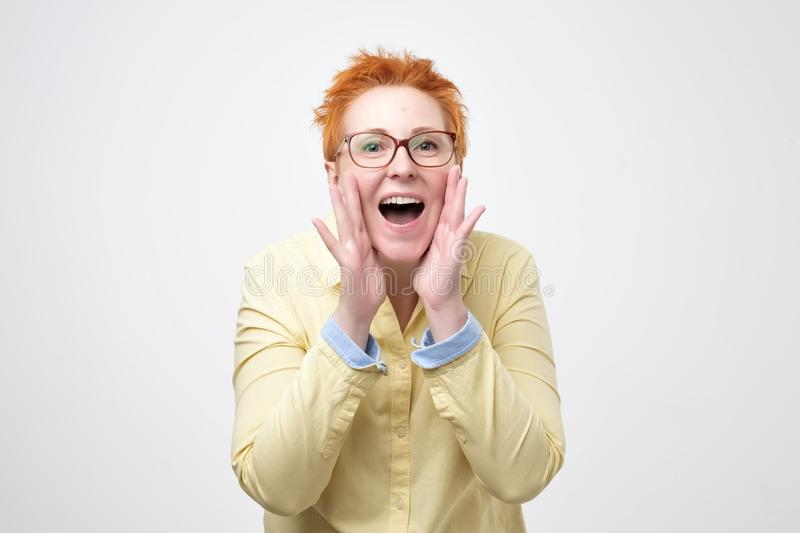 Do not tell anyone concept. Talkative prettyeuropean woman with red hair is saying secret hot braking news. Isolated on grey background stock image