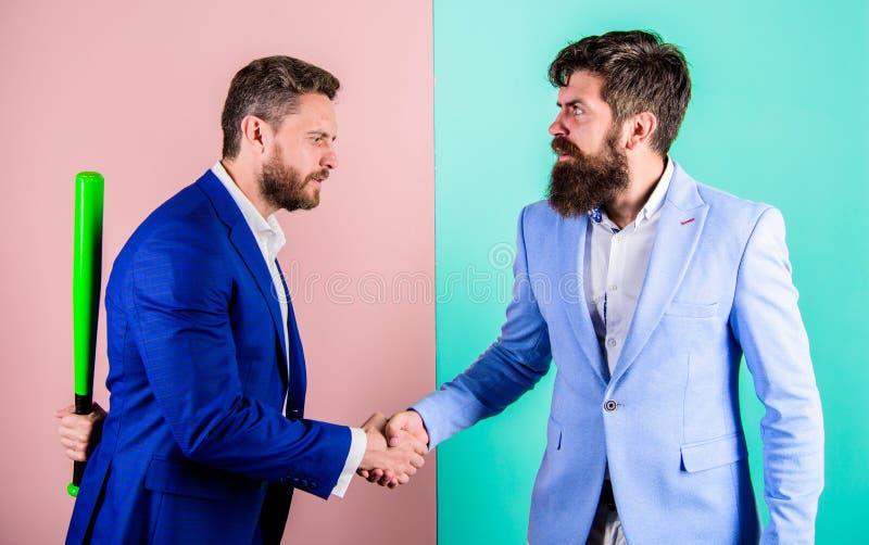 Do not trust him. Businessman hides bat behind back while shaking hands. Hidden threat concept. Business partners stock photo