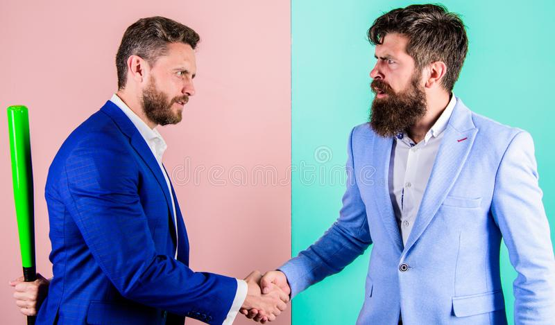 Do not trust him. Hidden danger. Businessman hides bat behind back while shaking hands. Hidden threat concept. Business stock photo