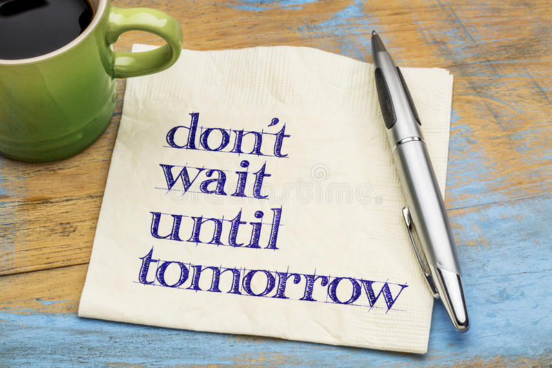 Do not wait until tomorrow. Motivational advice on a napkin with a cup of coffee stock image