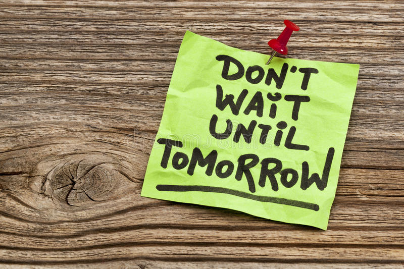 Do not wait until tomorrow. Motivational reminder - handwriting on sticky note against grained wood royalty free stock photos