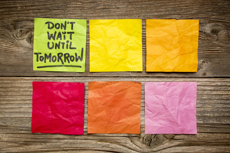 Do not wait until tomorrow note. Do not wait until tomorrow - motivational reminder - handwriting on sticky note against grained wood royalty free stock photo